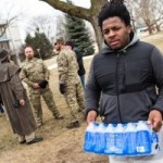 FLINT, MI - JANUARY 24:  Darius Simpson, an Eastern Michigan University student from Akron, Ohio, carries water he brought to donate for Flint residents during a rally on January 24, 2016 at Flint City Hall in Flint, Michigan.  The event was organized by Genesee County Volunteer Militia to protest corruption they see in government related to the Flint water crisis that resulted in a federal state of emergency.  (Photo by Brett Carlsen/Getty Images)
