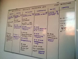 Dry erase board with weekly services and events offered at asylum seeker shelter