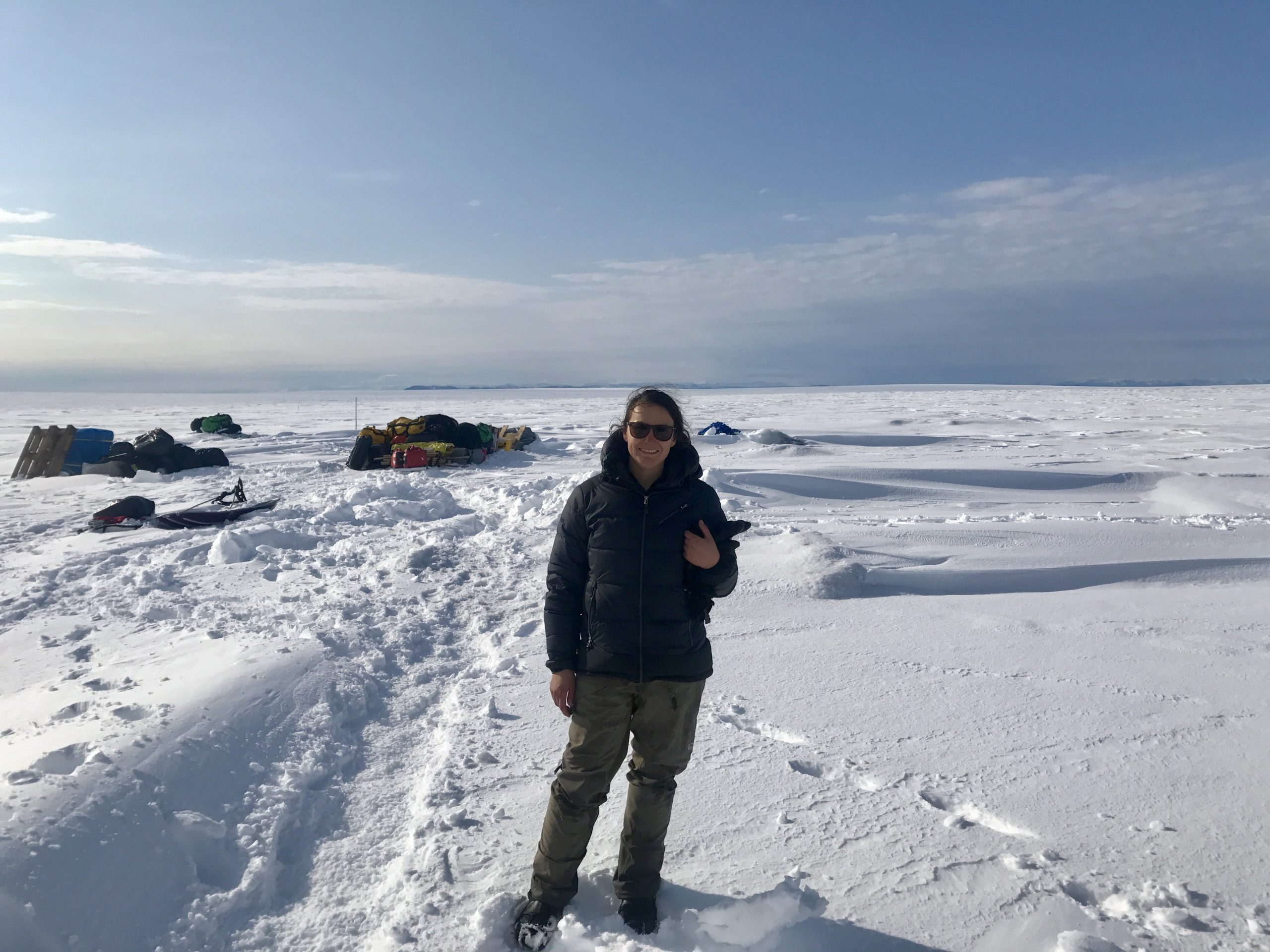woman in a navy parka and tan snow pants standing on a a flat snow-covered surface (Greenland Ice Sheet) Blue sky with clouds in the distance